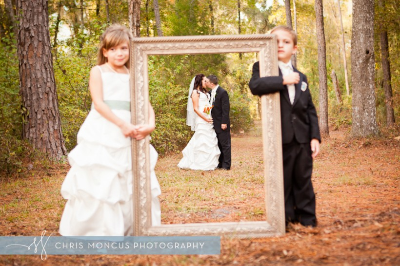Bride and Groom in frame held by ring bearer and flower girl in Tampa FL wedding